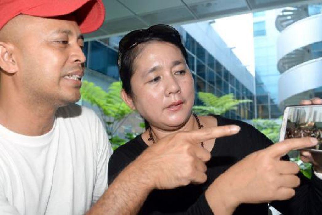 MASIH RAMAI: Cik Mega Suria dan suaminya Encik Ayub Ismail melihat beberapa foto yang menunjukkan suasana orang ramai beratur di Padang yang mereka rakam semasa menunggu di sana semalam. - Foto TAUFIK A. KADER