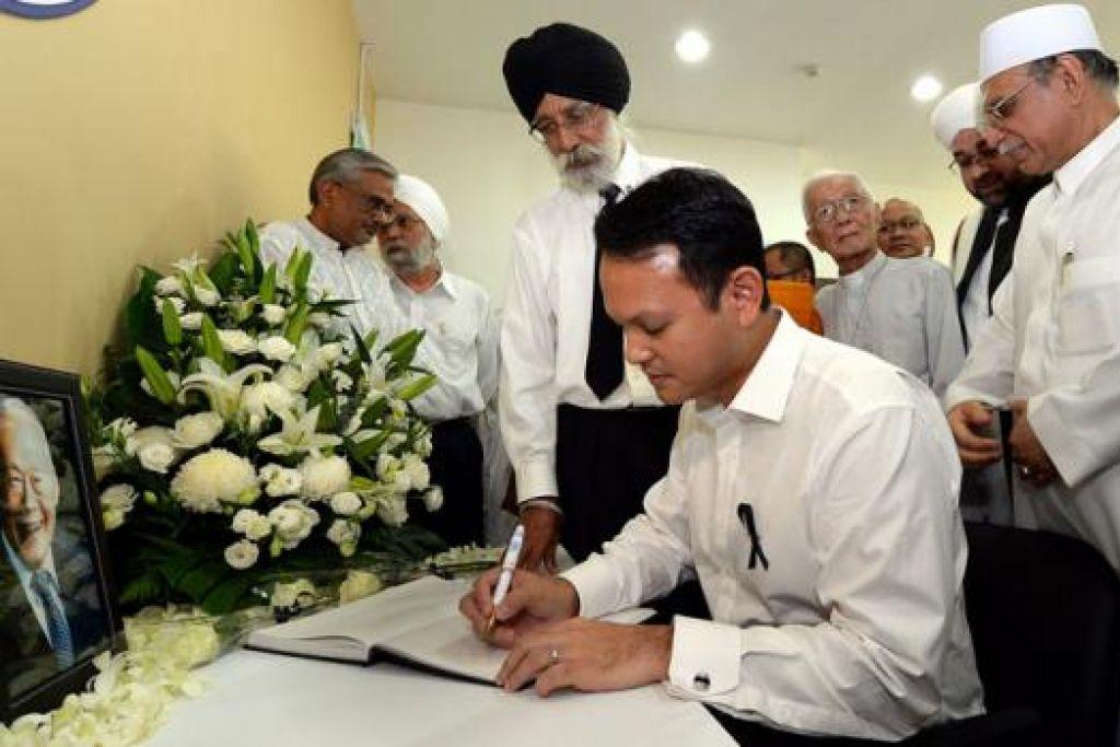 SENTIASA DIINGATI: Encik Zaqy menandatangani buku takziah bagi mendiang Encik Lee dengan disaksikan para wakil IRO termasuk Habib Hassan Al-Attas (kanan) dan Encik Gurmit Singh (bertali leher).