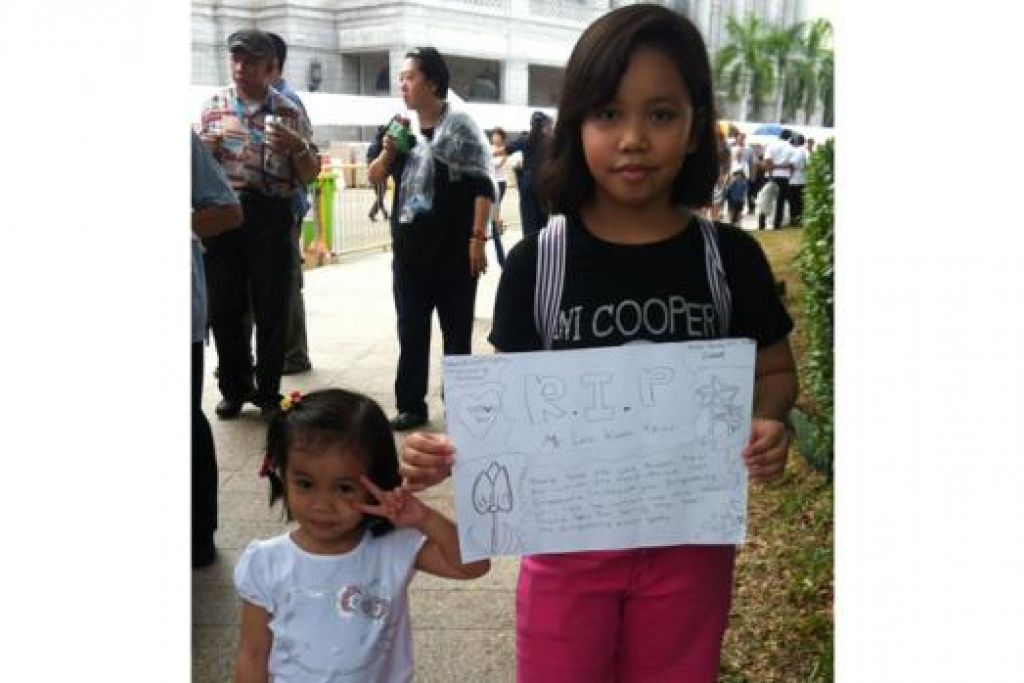 MEMBAWA LUKISAN: NurAqilah Alesha Mohammad Azlan, 11 tahun, membawa salah satu lukisannya semasa memberi penghormatan terakhir di Bangunan Parlimen semalam. Dia bergambar bersama adiknya, NurAlya Amani, tiga tahun. - Foto NURMAYA ALIAS
