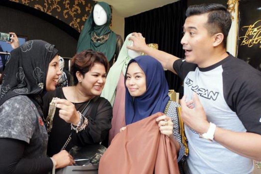SERONOK BERBELANJA: Pengalaman membeli baju Raya pastinya lebih manis apabila anda dilayan oleh selebriti terkenal Aaron Aziz (kanan) yang membantu isterinya, Diyana Halik (bertudung biru), menjual busananya dengan jenama diyanaxfatimah. Diyana bergabung dengan jurumekap popular, Fatimah Mohsin (di kanan Diyana) bagi koleksi ini. - Foto ZAKI RAZALI PHOTOGRAPHY