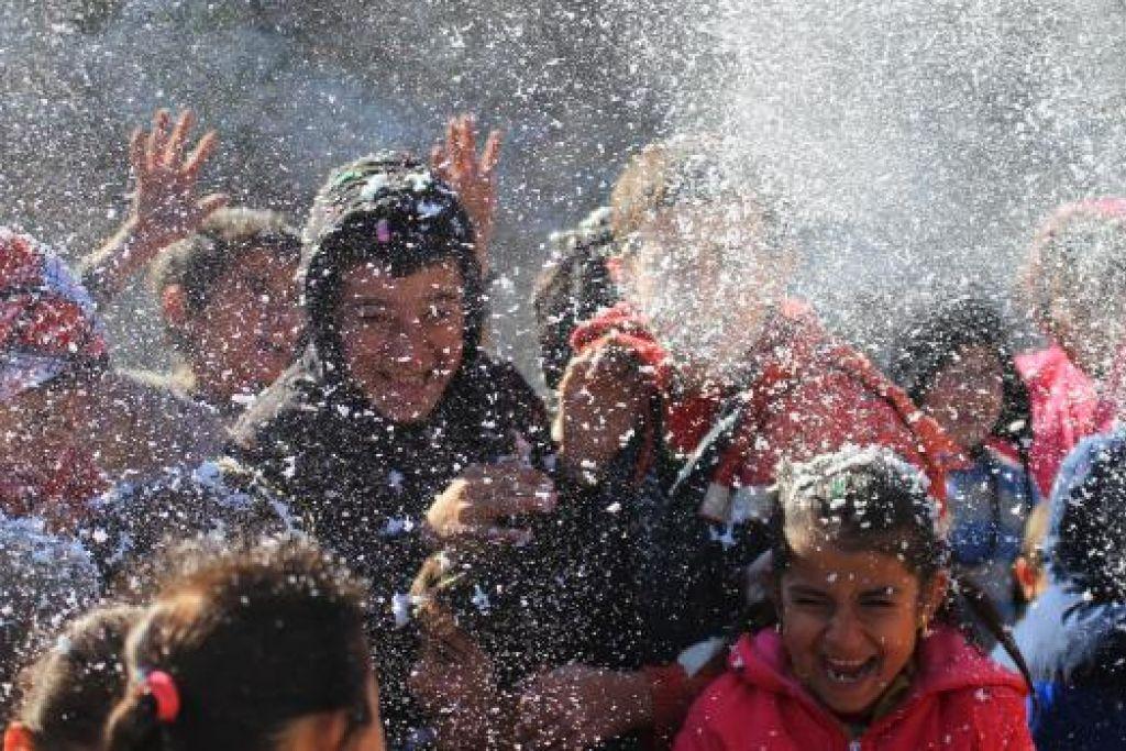 CERIA DALAM DUKA:  Kanak-kanak yang tiada tempat tinggal bermain dengan buih yang disemburkan oleh sukarelawan yang menghiburkan mereka di khemah-khemah sementara di wilayah Latakia, dekat sempadan Syria-Turkey pada 4 Disember lalu. - Foto REUTERS.