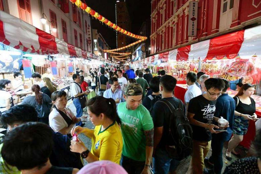 'IKAT PERUT': Oranga ramai membeli-belah sempena sambutan Tahun Baru Cina di Chinatown baru-baru ini. Tinjauan terbaru menunjukkan peruntukan perbelanjaan oleh warga Singapura bagi perayaan itu susut 11 peratus tahun ini. – Foto THE STRAITS TIMES