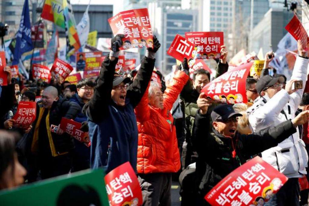SOKONGAN RAKYAT: Orang ramai meraikan keputusan Mahkamah Perlembagaan Korea Selatan yang mengekalkan keputusan memecat Presiden Park Geun Hye atas kesalahan rasuah. - Foto REUTERS