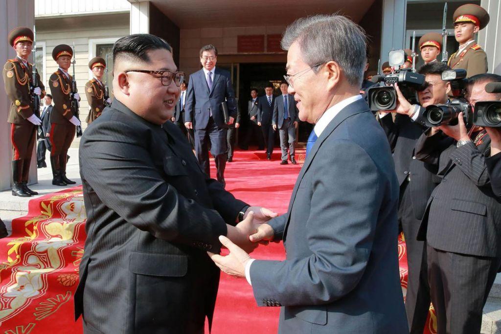 PERTEMUAN DUA PEMIMPIN: Ketua Korea Utara, Encik Kim Jong Un (kiri) berjabat tangan dengan Presiden Korea Selatan, Encik Moon Jae In, semasa pertemuan di desa kedamaian Panmunjom dalam kawasan bebas tentera di bahagian Utara. - Foto AFP