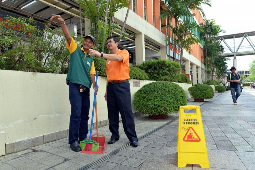 Encik Zainal Sapari bersama seorang pekerja pembersihan.