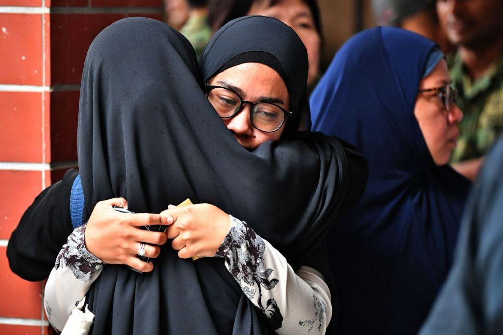 MENAHAN HIBA: Isteri Allahyarham, Cik Norsidah Kamilan, (tengah dan berkaca mata), tidak dapat menahan sebak semalam. - Foto BH oleh LIM YAOHUI