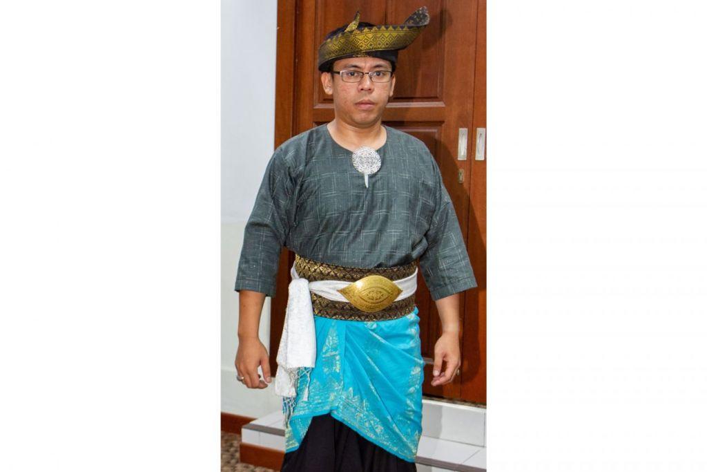 BUSANA LELAKI MELAYU LENGKAP: Encik Muhammad Fairuz menunjukkan cara pemakaian baju Melayu siap dengan kerongsang, pending dengan bengkung putih, bengkung daripada songket hitam hitam dan kain samping jenis songket berwarna biru. - Foto BH oleh ZALEHA ABDUL KADER