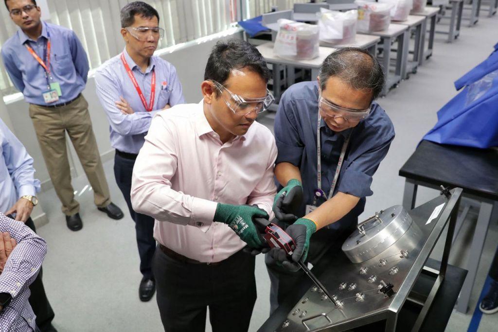 LANGKAH KESELAMATAN KERJA: Encik Zaqy (dua dari kanan) mendapat bimbingan pelatih, Encik Hu Hoi Seng (kanan), 57 tahun, semasa mengetatkan skru serta mengikat kabel keselamatan bagi mengelakkan kelonggaran pada pelantar latihan sewaktu pelancaran Kempen 'Safe Hands' 2019 di Singapore Aero Engine Services Private Limited (SAESL) semalam. - Foto KEVIN LIM
