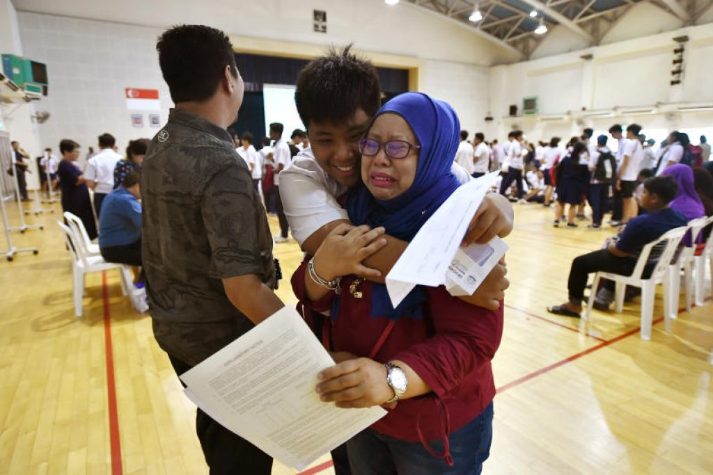 AIR MATA GEMBIRA: Pelajar, Norman Adli Ramli, 16 tahun, memeluk ibunya, Cik Norlizah Abdul Kahar, 40, yang bangga dengan keputusan anaknya yang membolehkannya melangkah ke maktab rendah. FOTO: LIM YAOHUI