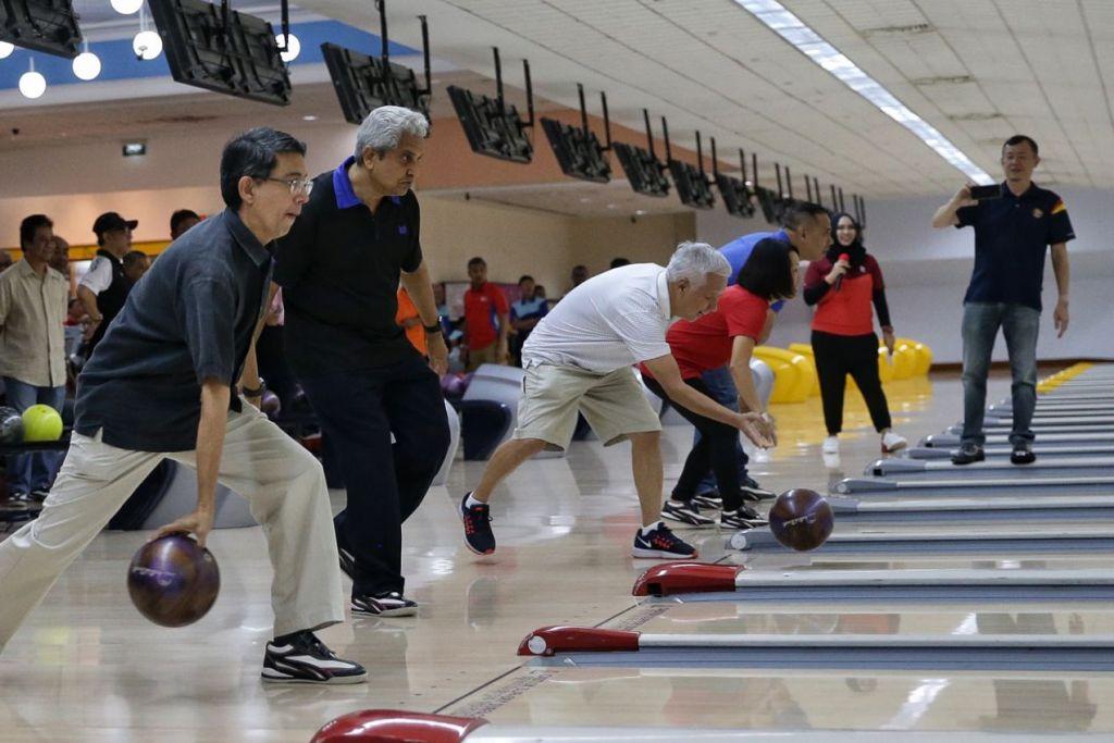 PERKUKUH JALINAN: Profesor Madya Muhammad Faishal Ibrahim (kiri sekali) memulakan acara bowling, 'Let's Strike Bowling 2019' bersama pemimpin kesatuan. - Foto BH oleh KEVIN LIM