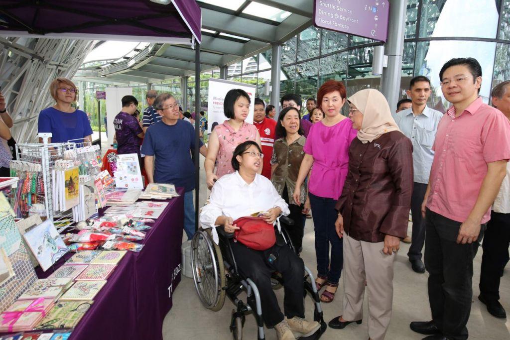 GALAK NIAGA SOSIAL: Presiden Halimah, diiringi Encik Wong (kanan), meninjau antara gerai perusahaan sosial yang ditampilkan sebagai sebahagian acara pasar lambak semalam. - Foto ZAOBAO