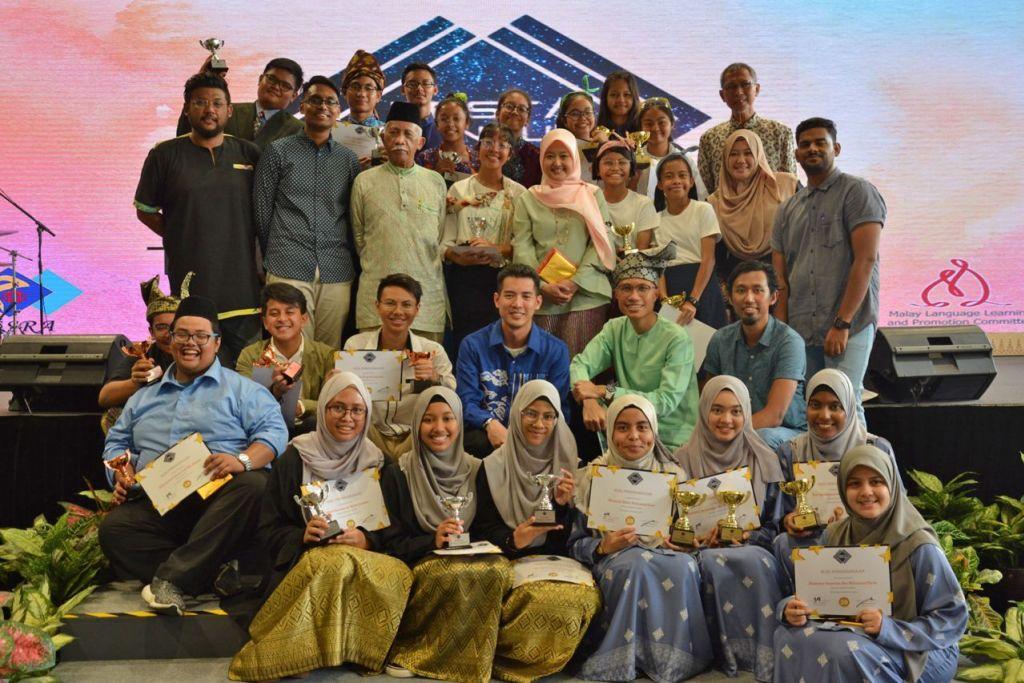 DIRAI: Para pemenang peraduan Pesta Pantun mengambil gambar bersama-sama disertai tetamu terhormat Cik Rahayu (berdiri tengah, bertudung). - Foto PBMUKS