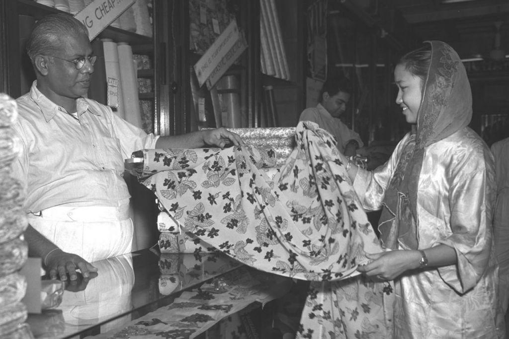MANA SATU PILIHAN HATI?: Wanita ini sedang membelek-belek kain untuk dijadikan baju Raya yang bakal menjelang. Gambar ini dipetik pada tahun-tahun 1950-an. - Foto fail