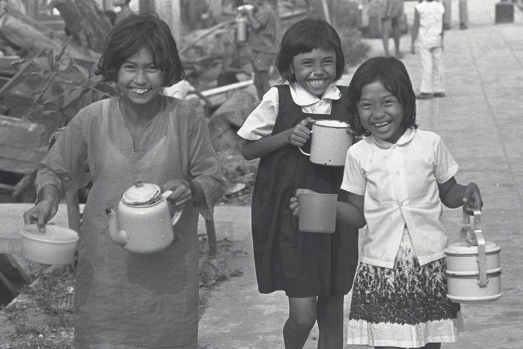 GEMBIRANYA DAPAT BUBUR: Keceriaan jelas terpancar pada wajah kanak-kanak ini yang membawa pulang bubur yang diagihkan Masjid Aminah yang terletak di kawasan Geylang pada tahun-tahun 1960-an dan 1970-an. - Foto fail