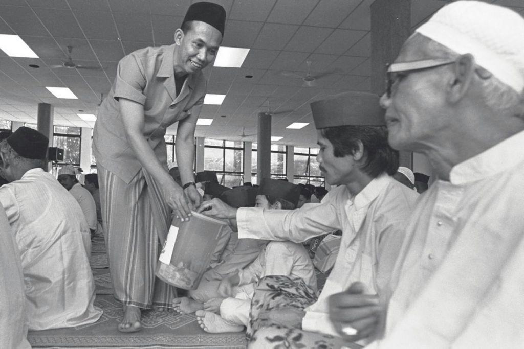 ISI 'TABUNG' SEMPENA SOLAT TARAWIH: Pegawai Masjid Jamiyah Al Rabittah di Tiong Bahru'mengelilingi' jemaah dengan tabung masjid di salah satu sesi solat tarawih. Gambar ini dipetik pada 1985.  - Foto fail