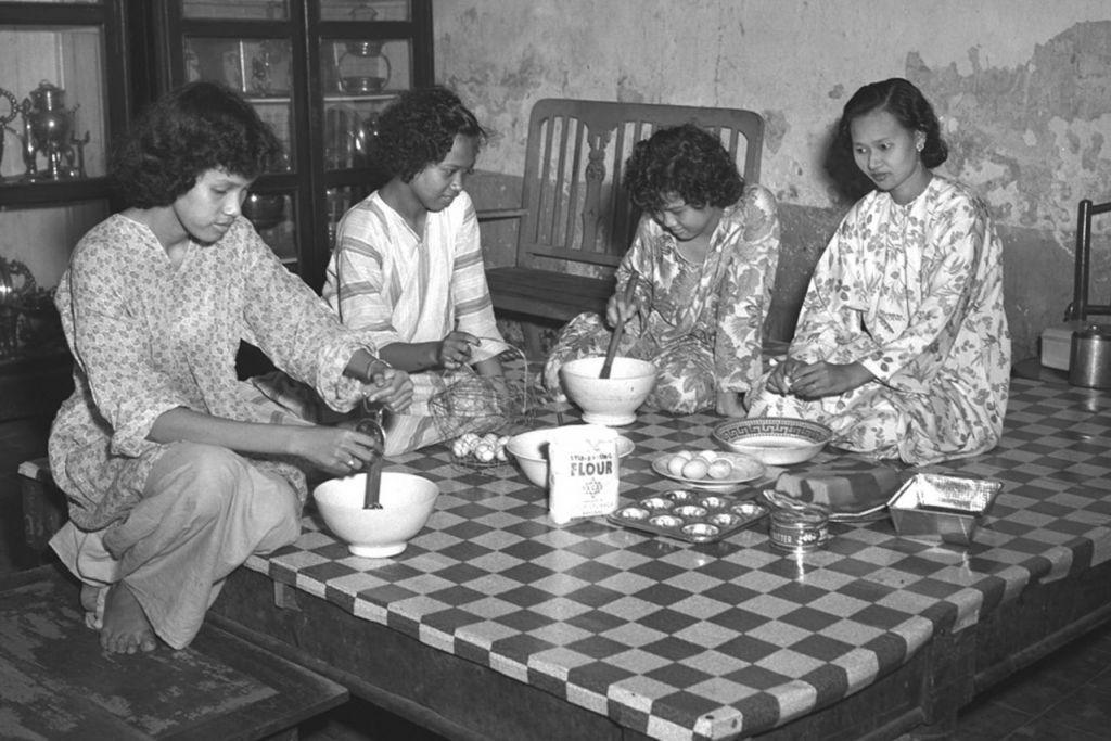 SENGKANG MATA, BUAT KUIH: Sekumpulan wanita saling membantu satu sama lain semasa menyediakan kuih-muih yang bakal disajikan apabila tiba Raya nanti. Foto ini juga dipetek pada tahun-tahun 1950-an.  - Foto fail