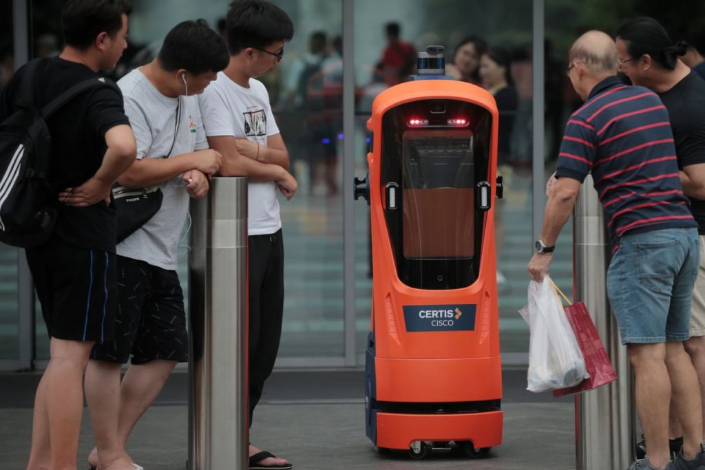 ERA TEKNOLOGI DAN AUTOMASI: Pengunjung di Jewel Lapangan Terbang Changi melihat secara dekat robot autonomi kendalian Certis Cisco pada 4 Jun lalu. Menurut penulis, rakyat Singapura perlu belajar untuk bekerja bersama robot untuk melangkah lebih jauh ke hadapan. - Foto BH oleh JASON QUAH