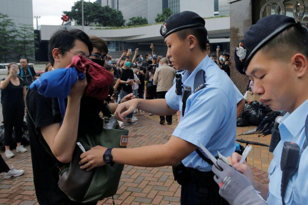 KAWALAN KETAT: Pegawai polis memeriksa beg seorang pejalan kaki ini di Hongkong semalam - sehari selepas insiden keganasan yang menyaksikan penunjuk perasaan bertempur dengan polis. - Foto REUTERS