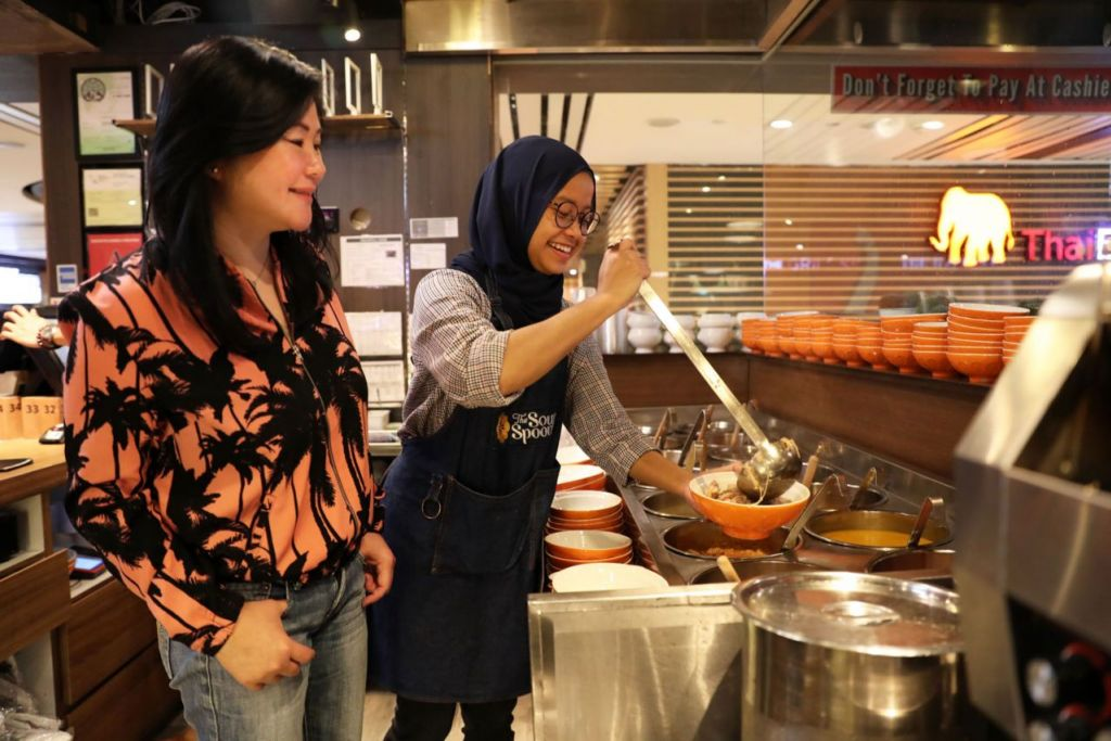 DAPAT PERHATIAN: Sup yang disediakan seorang kakitangan, Cik Siti Nurzana Abd Hamid, dan diperhatikan Cik Anna Lim (kiri) terus dapat perhatian di restoran The Soup Spoon Union yang menggabungkan tiga jenama lain. - Foto BM oleh GIN TAY