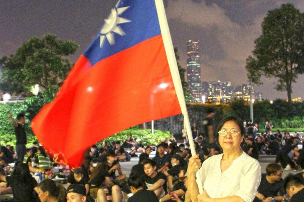 TUNJUK BANTAHAN: Penduduk Hongkong, Cik Yung Xiu Kwan, 67 tahun, bergambar dengan memegang bendera Taiwan semasa membantah terhadap undang-undang ekstradisi yang dicadangkan yang membolehkan orang di Hongkong dihantar ke tanah besar China. - Foto REUTERS