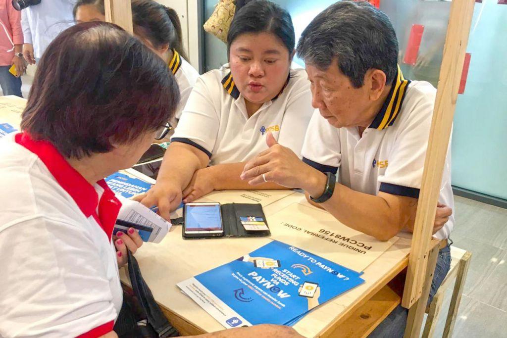 SAHUT CABARAN BARU: Antara skop tugasan baru Cik Nur Syahida (tengah) adalah mengajar pelanggan memanfaatkan saluran atau khidmat digital perbankan yang ditawarkan bank DBS. - Foto DBS